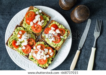 Avocado toast. Healthy toast with avocado mash, cherry tomatoes and crumbled feta cheese on a plate. Table top view