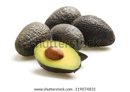 Avocados, one cut in half, photographed on a white background.