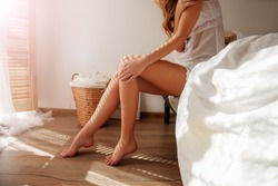 Awakened Woman Sitting on the edge of the Bed looking out the Window, bare Feet on the Floor. Side view, cropped Photo of Beautiful Female Legs. Spring rays of the sun penetrate through wooden blinds