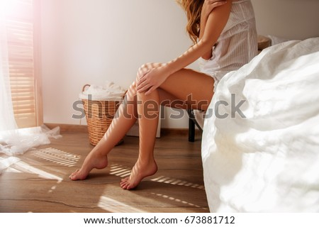 Awakened Woman Sitting on the edge of the Bed looking out the Window, bare Feet on the Floor. Side view, cropped Photo of Beautiful Female Legs. Spring rays of the sun penetrate through wooden blinds  #673881712