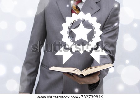 Award Quality Medal Education Business concept. Businessman holds book with award medal icon on a virtual screen.