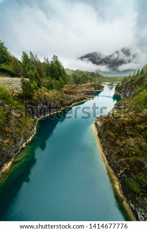 Awe hanging bridge at north Chilean Patagonia, Puelo river moves around the narrow gorge with its turquoise waters on an awe idyllic natural environment outdoor rugged landscape under a dramatic sky  #1414677776