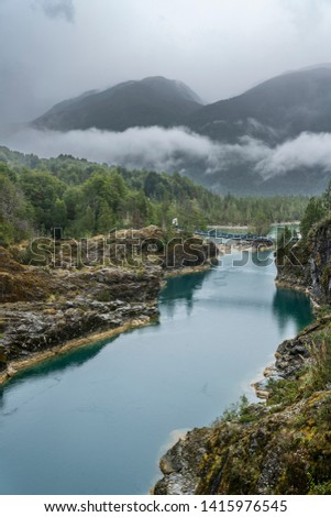 Awe hanging bridge at north Chilean Patagonia, Puelo river moves around the narrow gorge with its turquoise waters on an awe idyllic natural environment outdoor rugged landscape under a dramatic sky  #1415976545