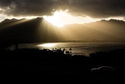 Awe inspiring rays of sun come down over the mountain range.