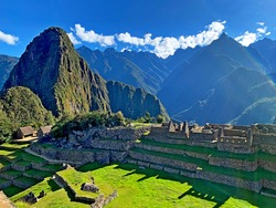 Awe Machu Picchu legendary lost city of Inca Empire in Peru, Andes mountains. Majestic historical complex landmark, ancient stone buildings, green grass terraces , Inca Trail in Huayna Picchu mount.