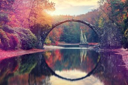 Awesome Autumn Landscape. Amazing sunset in Azalea and Rhododendron Park Kromlau. Rakotz Bridge, Rakotzbrucke Devil's Bridge in Kromlau, Saxony, Germany. Creative Artistic image. Picturesque Nature
