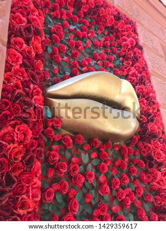 Awesome awesome background image of two yellow lips in the middle of the red roses designed on the wall.