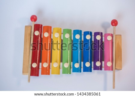 Awesome awesome colorful rainbow colored children's toy musical instrument stands on white background Buying great contrast in different colors angles concept macro shot detail in vivid.