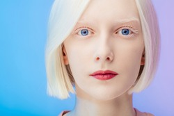 awesome beautiful albino with makeup and blue eyes looking at the camera, close up photo. isolted on the blue background, studio shot