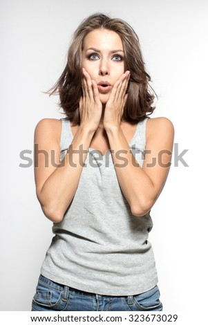 Awesome Caucasian attractive joyful happy sexy female model with brunette hair is grimacing in studio, wearing grey sleeveless shirt, isolated on white background
