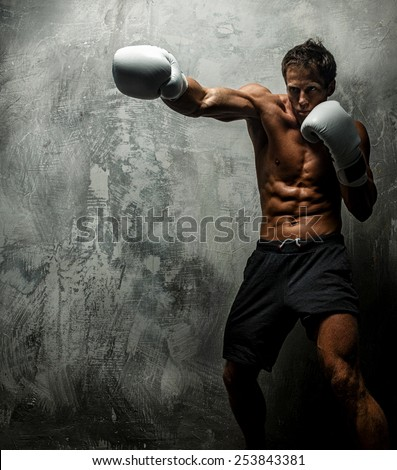 Awesome female with great antomy boxing. Grey background.