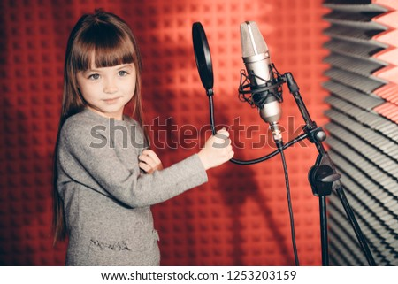 awesome little girl singing songs in the music recording studio. close up photo.spare time, free time