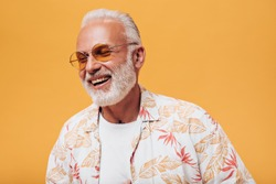 Awesome man in orange eyeglasses laughing on isolated background. Gray-haired adult with beard in light outfit is smiling into camera