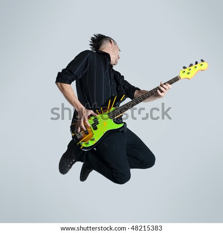 Awesome mohawk man jumps with his guitar in studio