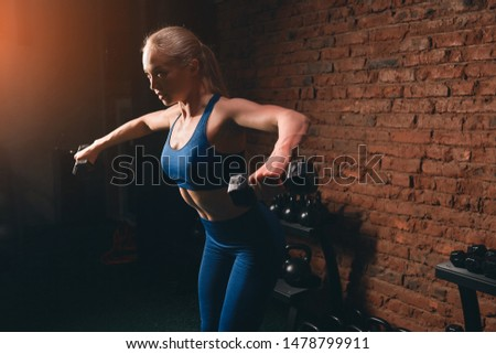 awesome motivated girl with raised arms trying to hold dumbbells. endurance concept. close up side view photo.endurance