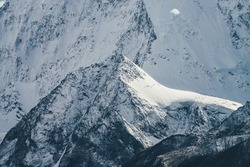 Awesome mountain landscape with big snow rock with peaked top on background of giant snow-covered mountain wall in sunshine. Atmospheric scenery with snowy mountains in sunlight. Great snowy mountains