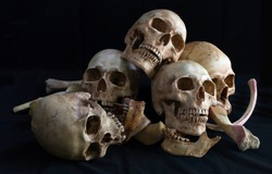 Awesome pile of skull and bone on black cloth background, Still Life style, selective focus