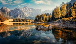 Awesome sunny landscape in the forest. Wonderful Autumn scenery. Picturesque view of nature wild lake. Sun rays through colorful trees. Incredible view on mountains lake. Amazing natural Background