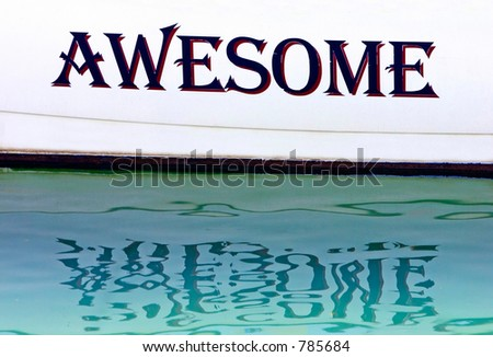 Awesome written on the side of a boat in Spain with the letters reflecting in the water