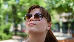 Awesome young caucasian woman lookingup in park with cool reflection in her sunglasses. Bright Sunny day in summer.