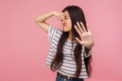 Awful smell! Portrait of confused girl with brunette hair pinching her nose to hold breath and showing stop gesture, disgusted by unpleasant odor, fart. indoor studio shot isolated on pink background