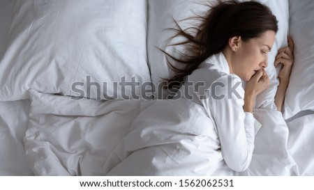 Awoken lonely scared young woman insomniac lying in bed alone suffer from insomnia or disturbing nightmare dream feel depressed anxious worried of problem afraid can not sleep concept, above top view