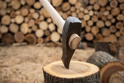 Ax stuck in stump bokeh. Woodcutter's ax on the stump. Wooden stump in the forest. Deforestation man. Felled tree.