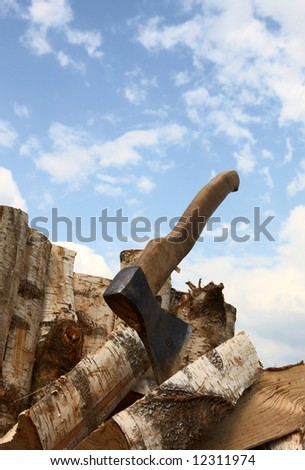 Axe and logs on a background of the sky