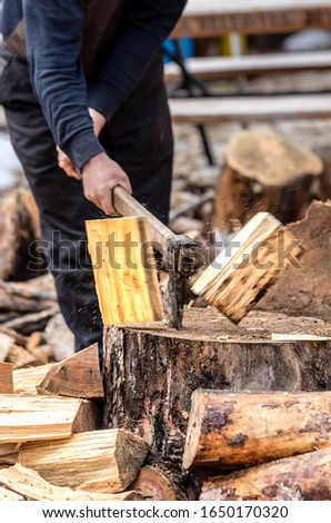 Axe firewood, hands of a old man splitting wood with an axe, focus is on the axe, motion freezing in the moment it split