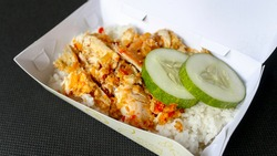 Ayam geprek or Spicy chicken crush with chilli and garlic flavour on white plate isolated on white background. Indonesian culinary spicy food.