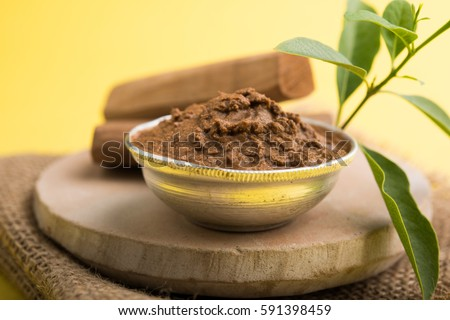 Ayurveda and body care - Chandan or sandalwood paste in silver bowl with sticks and leaves placed over stone base which is used for creating paste. Selective focus