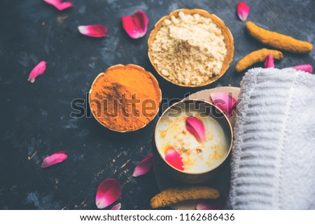 Ayurvedic face pack/mask using Gram Flour/besan, Haldi & milk ubtan placed in brass bowls with rose petals, scrub  and white napkin. selective focus