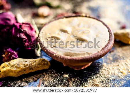 Ayurvedic ubtan of Haldi with holy rose water and fuller's earth on wooden surface for good, brighter, and softer skin.