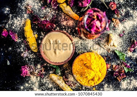 Ayurvedic ubtan of turmeric/haldi and mulpani mitti or fuller's earth with rose water on a black surface for good skin and brighter skin with no acnes and pimple free.
