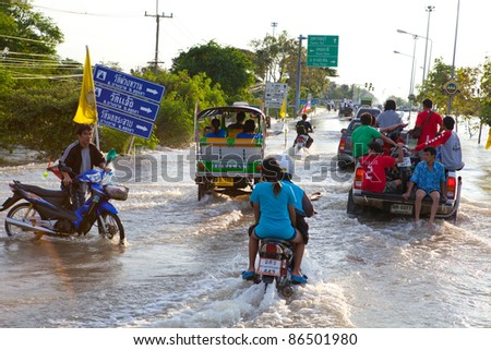 AYUTTHAYA, THAILAND - OCTOBER 9: Pickup truck and motorcycle transporting flood victims through the streets of the city during the worst monsoon flood. October 9, 2011 in Ayutthaya, Thailand.