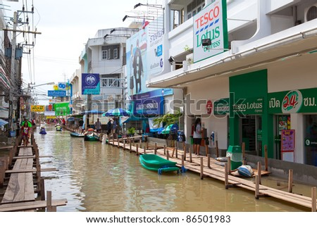 AYUTTHAYA, THAILAND - OCTOBER 9: Villagers floating through deep water on small boat during the monsoon flooding of October 9, 2011 in Ayutthaya, Thailand.