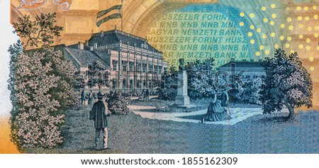 Az Ideiglenes Magyar Kepviselohaz Pesten (The Provisional Assembly of Hungary in Budapest) building with flag, trees, strolling couples, and statue of bust. Portrait from Hungary Banknotes.  Stock fotó ©