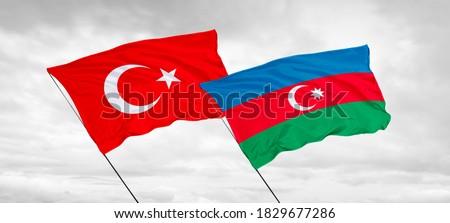 Azerbaijan and Turkey flags waving in the dawn sky