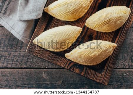 Azerbaijan national dessert. Oriental Sweet Pastry Dessert - Shekerbura on wooden board on wooden table background. Top view, copy space