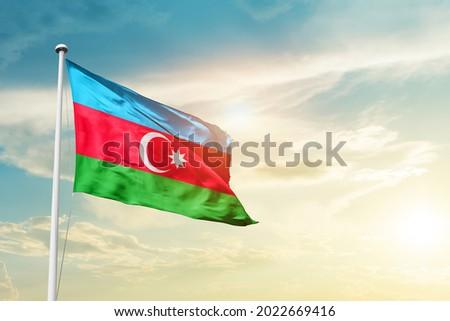 Azerbaijan national flag waving in beautiful clouds.