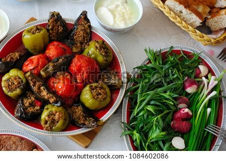 Azerbaijani dolma with eggplant, tomato and pepper, yogurt, greenery and bread on the table