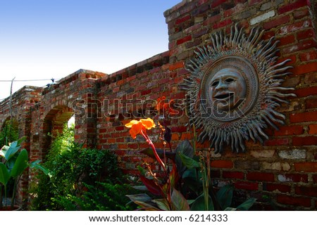 Aztec sun disk on brick wall in a garden