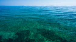 Azure blue and green water surface of Ionian sea near to the beach as background image with horizon