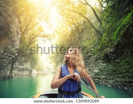 azure mountain river glistens in sun, charming happy smiling girl with lush blond hair sits in boat on lake in Georgia, nature Martvili Canyon, rafting as active leisure for tourists, bright sunshine