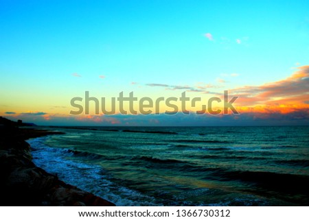 Azure sky with low clouds over the waving Adriatic sea during a splendid sunset
