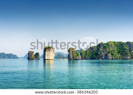 Azure water of the Ha Long Bay at the Gulf of Tonkin of the South China Sea, Vietnam. Scenic view of blue lagoon and karst towers-isles. The Halong Bay is a popular tourist destination of Asia. #386346205