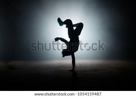 b-boy performing kick on yhe dark street. stylish position. dance form