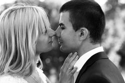 B&W beautiful elegant  blonde bride kissing handsome brunette groom close-up