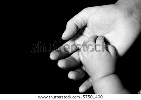 B&W photo of new-born baby hand in mother's palm, isolated on black background.