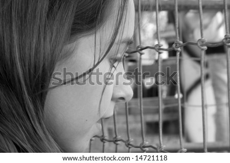 B&W photo of ten year old girl looking into an animal cage
